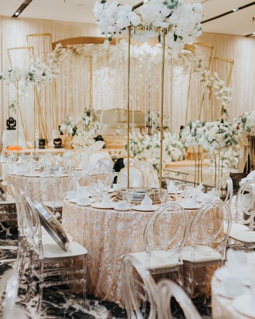 Phía bên trong sảnh tiệc là các bàn tròn phủ khăn trải bàn màu vàng. Uyên ương sử dụng ghế tàng hình nhưng có lót đệm trắng bên trên, mang đến sự hiện đại cho không gian làm lễ.