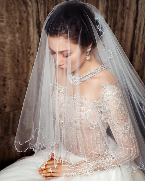 Phần cổ áo được thiết kế kiểu jewel neckline (cổ áo trang sức) và kết nối với váy nhờ phần voan mỏng.