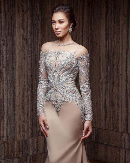 Chiếc váy thứ hai mà cô dâu diện để cắt bánh cũng đến từ NTKRizman Ruzaini. Bộ đầm có nhiều điểm tương tự với váy cưới chính khi cũng sử dụng cổ áo jewel neckline, phần thân trên họa tiết ren, đá hoàng gia. Riêng thân dưới là vải trơn màu ngà.