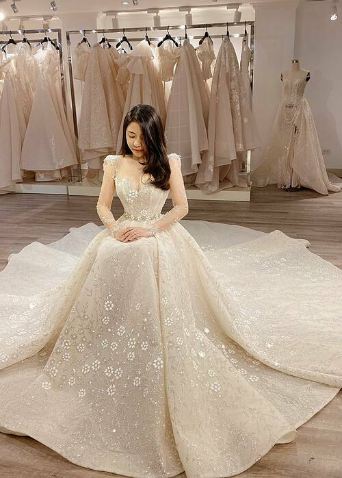 Phần tà váy xếp nếp tạo dáng như một bông hoa nhiều cánh. Khi cô dâu ngồi xuống, những cánh hoa ấy xòe rộng sang hai bên khiến chiếc váy mang hình dáng của một bông hoa ở thời điểm nở rộ nhất, xinh đẹp nhất.