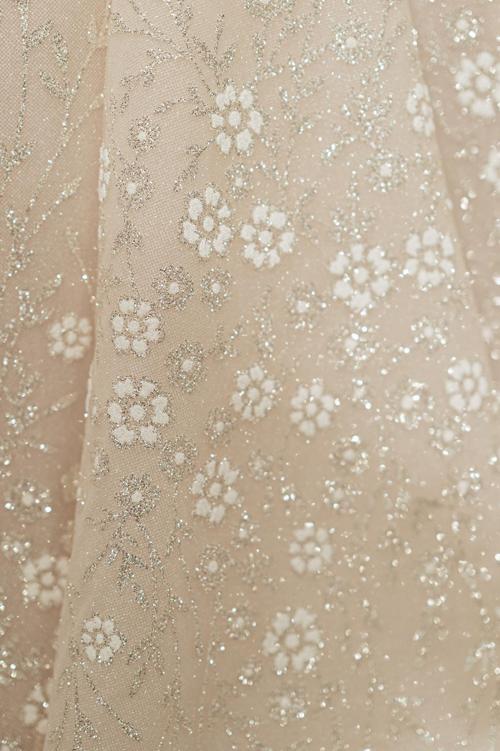 Một điểm đặc biệt khác được NTK tiết lộ chính là những bông hoa nhũ trắng được dập nổi trên trên váy. Chính sự tương phản giữa sắc trắng của các bônghoa và lớp vải tuyn tone nude đã giúp bản thiết kế trở nên cuốn hút.