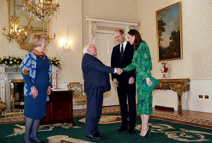 Kate cởi áo khoác màu xanh đậm khi vào trong dinh thự. Bà mẹ ba con mặc váy xanh hoạ tiết hoa, và cầm clutch cùng màu. Cô cũng đi giày và đeo bờm tóc ton sur ton với chiếc cà vạt của Hoàng tử William. Ảnh: Reuters.