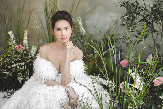 Váy cưới trễ vai xẻ ngực đính lông vũ giúp Ngọc Trinh khoe vòng một căng tròn. Phom váy được dựng dáng corset để tôn vòng eo con kiến.