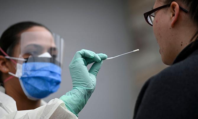 Một nhân viên y tế lấy mẫu bệnh phẩm của bệnh nhân. Ảnh: BI.