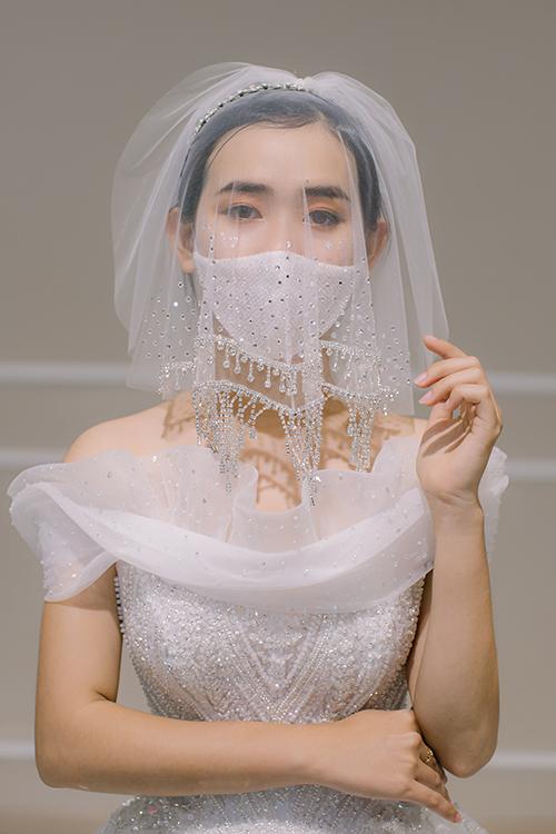 Chiếc khẩu trang điệu đà được kết hợp với khăn voan đính cườm, giúp cô dâu phòng chống dịch hiệu quả. Mẫu đầm tên Rinnie, có giá bán 120 triệu đồng, giá thuê 60 triệu đồng. Váy cách điệu nơi cổ áo, giúp thân hình người diện trở nên đầy đặn hơn.
