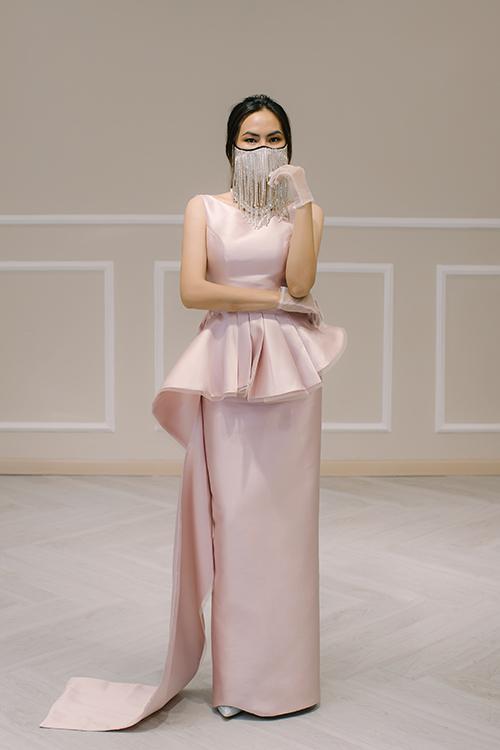 Một gợi ý khác cho cô dâu để chào bàn là váy Charming, có giá bán 4,5 triệu đồng. Váy mang tông hồng pastel, có điểm nhấn là phần vải nhún nơi eo và kéo thành tà phụ dài. Khẩu trang được đính đá không khác gì một phụ kiện trang sức cho bộ cánh.