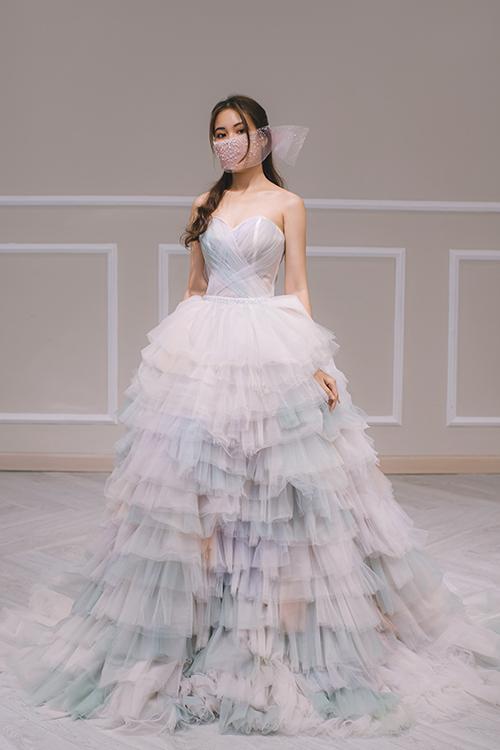 Váy Akori được làm từ kỹ thuật xếp ly, phối trộn từ nhiều sắc màu ngẫu hứng, mang đến vẻ trẻ trung cho người diện. Khẩu trang đi kèm mang tông hồng, được đính hạt ngọc. Váy có giá bán 40 triệu đồng, giá thuê 20 triệu đồng.