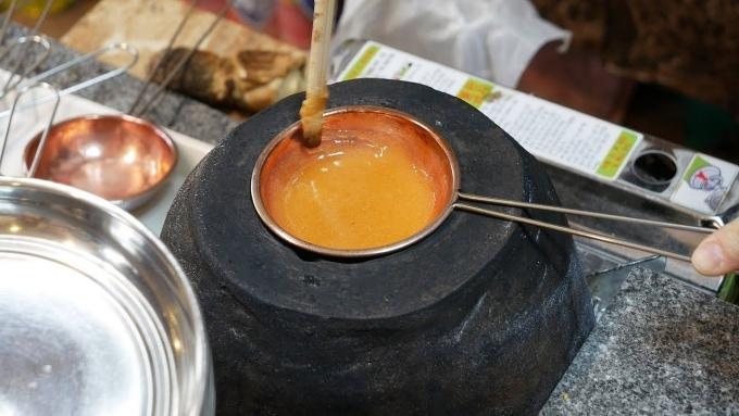 Cách làm kẹo dalgona ở Hàn Quốc, dùng một chảo nhỏ đun chảy hỗn hợp baking soda và đường là xong.