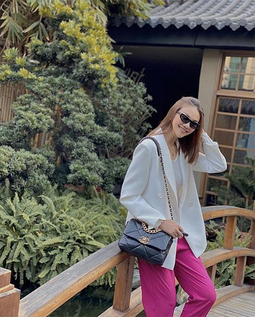 Công thức phối màu trắng - hồng - đen được Thanh Hằng xử lý khéo léo trên set đồ gồm áo blaze, quần đáy thụng và túi Chanel.