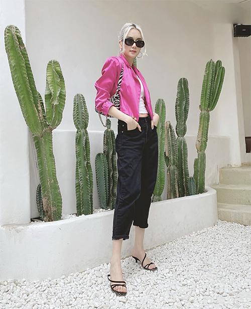 Áo jacket dáng lửng được Thiều Bảo Trang chọn làm điểm nhấn cho set đồ trẻ trung với áo hở eo, quần jeans xắn gấu, sandal và shouder bag.
