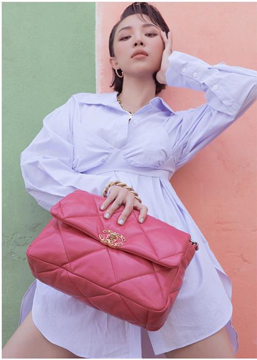 Diện váy sơ mi biến tấu với những đường nét phá cách ngoạn mục, Tóc Tiên chọn túi Chanel tông hồng nữ tính để tạo điểm nhấn.