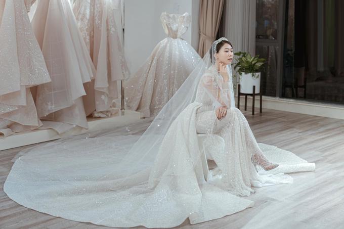 Váy cưới của Nina Lê cũng là một thiết kế 2 trong 1 với phần cổ trang sức (jewel neckline) và đính hàng ngàn viên pha lê trên thân váy.
