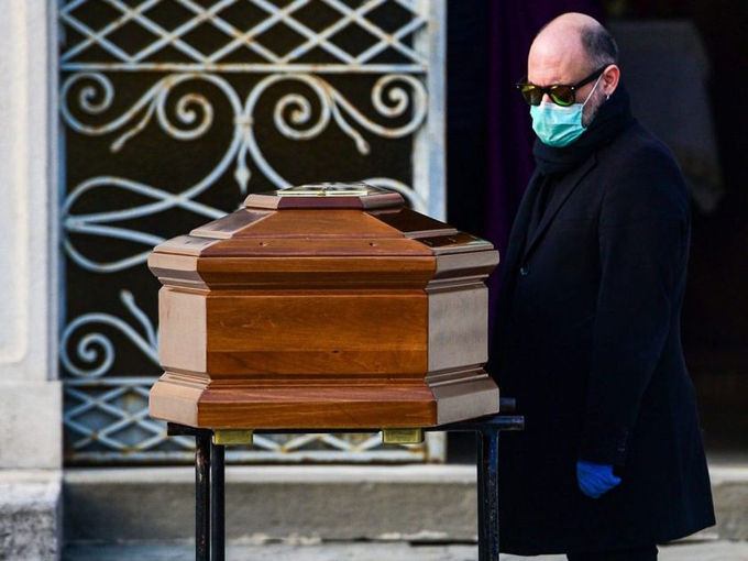 Một người đàn ông đứng bên quan tài mẹ ở nghĩa trang Seriate, gần thành phố Bergamo, Italy, hôm 20/3. Ảnh: AFP.