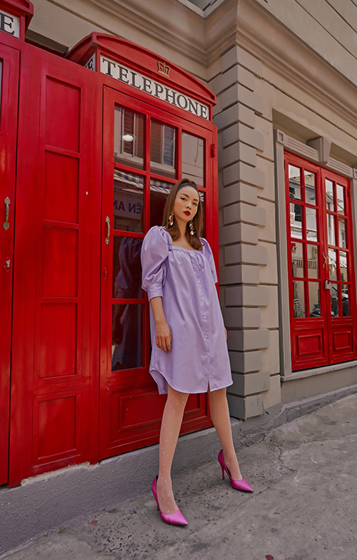Váy suông không kén dáng là kết quả giữa phép cộng giữa áo blouse và đầm sơ mi. Trang phục thiết kế trên màu tím pastel gợi hình ảnh thanh lịch, lãng mạn cho người mặc.