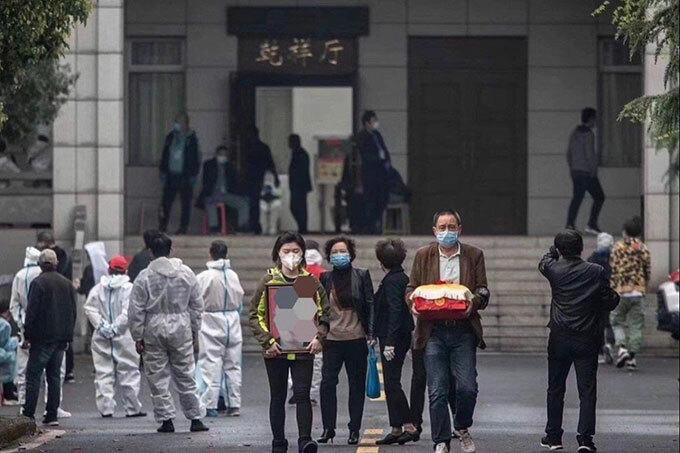 Một gia đình Vũ Hán đến nhận tro cốt người thân hôm 27/3. Ảnh: Weibo.