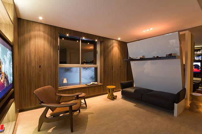 Chiếc ghế bành và ghế đẩu chiếm vị trí nổi bật trong không gian, giúp tạo điểm nhấn. Để tối ưu diện tích, gia chủ sử dụng chủ yếu nội thất đa chức năng. Chiếc giường gấp ẩn ngay sau bộ ghế sofa.