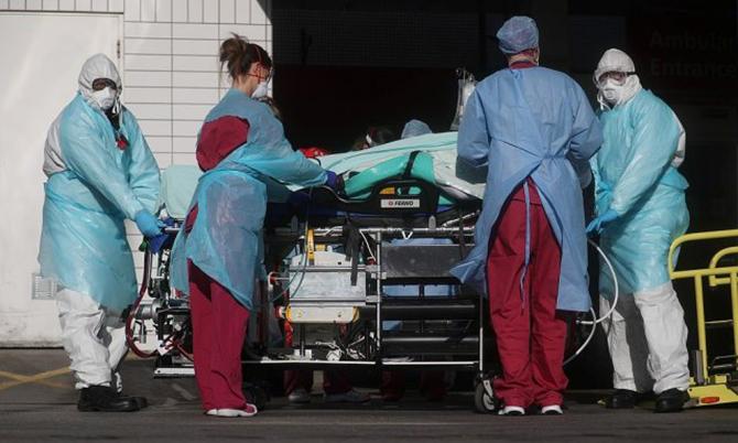 Các bác sĩ bệnh viện St Thomas, London tiếp nhận một bệnh nhân nghi nhiễm Covid-19. Ảnh: Reuters.