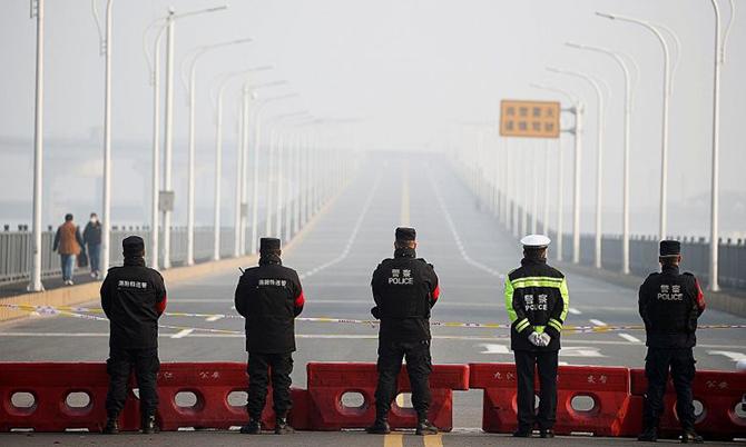 Cảnh sát đứng chặn giữa cây cầu nối thành phố Vũ Hán và tỉnh Giang Tô khi lệnh phong tỏa được áp dụng hôm 23/1. Ảnh: Xinhua.