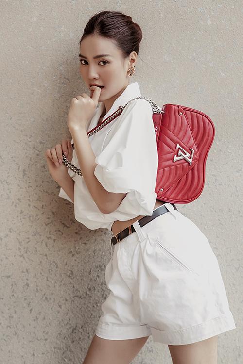 Suit trắng với sự kết hợp của áo hở eo cùng quần short được tăng sức hút với túi hiệu tông đỏ tươi.