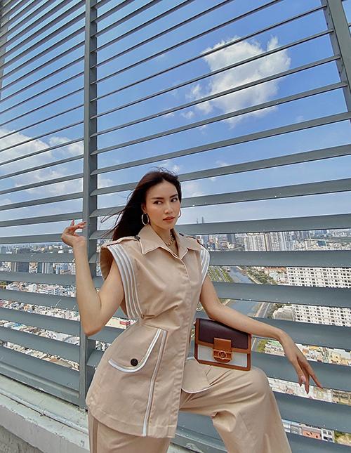 Suit kiểu dáng độc đáo với phần ống tay to bản đi kèm đường viền trắng trên nền trang phục tôn trung tính. Lan Ngọc chọn túi Louis Vuitton tông nâu pha trắng để phối đồ.