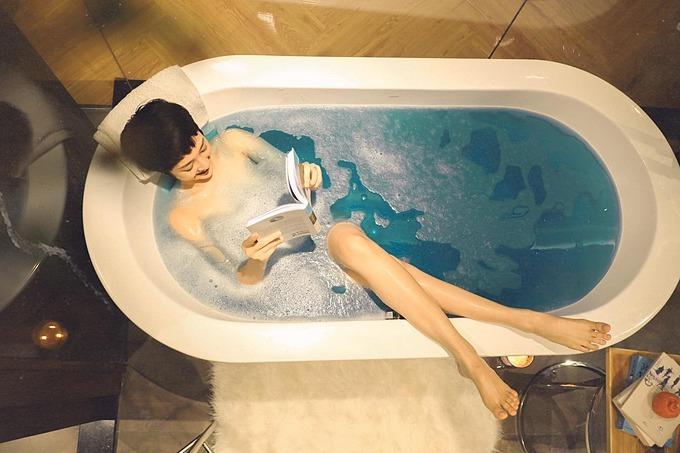 Ca sĩ Bảo Anh tranh thủ đọc sách khi ngâm mình trong bồn tắm.