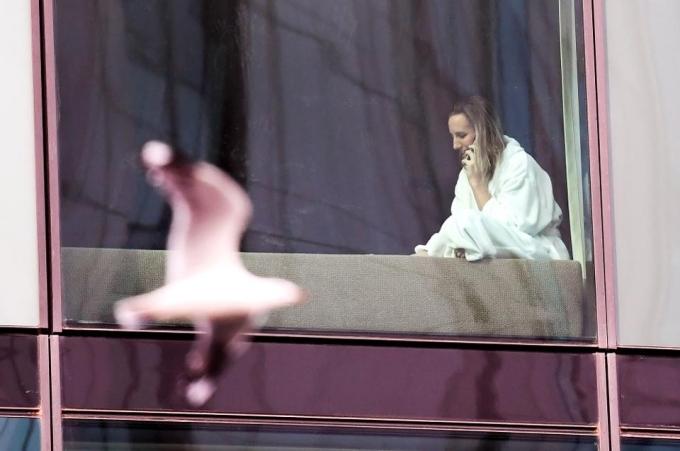 Một phụ nữ đang nghe điện thoại khi cách ly trong khách sạn hạng sang tại Melbourne. Ảnh AFP