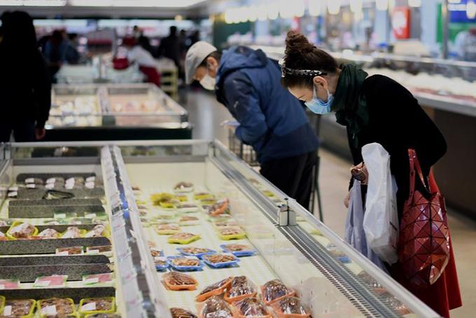 Người Vũ Hán giữ khoảng cách khi mua thực phẩm tại siêu thị hôm 30/3. Ảnh: AFP.