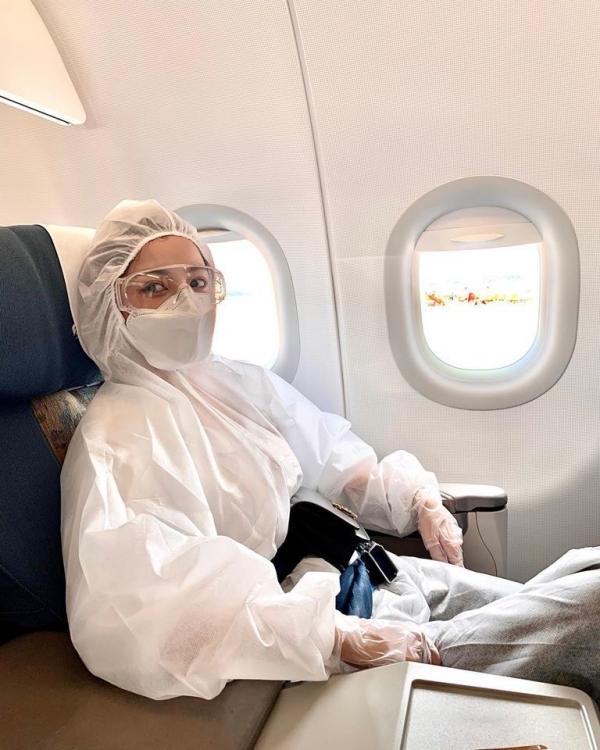 Chi Pu diện đồ bảo hộ trên chuyến bay về Hà Nội hồi tháng 3.