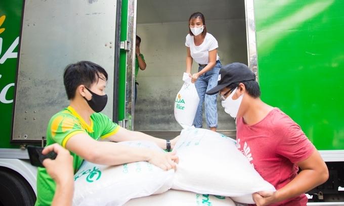 Sáng sớm 21/4, người đẹp có mặt tại điểm phát gạo từ thiện, cùng các nhân viên của hãng gạo vận chuyển gạo đổ đầy vào ATM gạo.