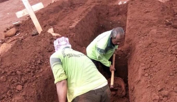 Ông Minar (không đội mũ trùm đầu) cùng một người trong nhóm đào huyệt trước khi xe cứu thương đưa thi thể người chết tới nghĩa trang. Ảnh: CNA.