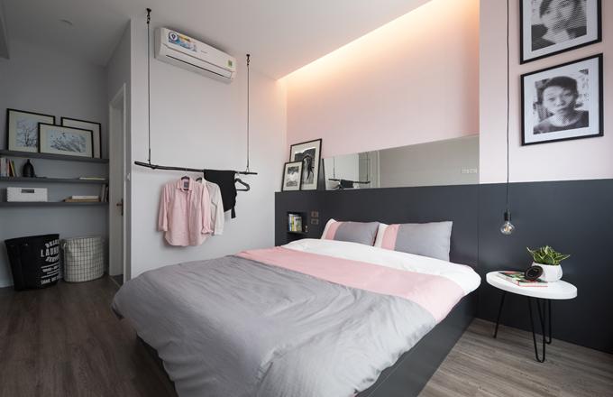 Phòng ngủ của cặp vợ chồng có diện tích hạn chế nên KTS chọn nội thất đơn giản, gọn gàng, bổ sung dải gương đầu giường để giúp không gian có vẻ thông thoáng, rộng rãi hơn. Những chi tiết chiếu sáng âm (giấu được nguồn sáng) được khai thác triệt để tạo hiệu ứng chuyển sáng êm dịu trong phòng ngủ, tạo sự thư giãn, giúp gia chủ được nghỉ ngơi. Căn phòng sử dụng móc treo bằng gỗ cho quần áo sử dụng trong ngày.Ngoài việc hợp lý hóa không gian cho những đề xuất của gia chủ, KTS bổ sung một số giải pháp để xử lý những góc nhỏ, nhọn trong căn nhà, xử lý hiệu ứng thị giác nơi trần, tường nhà, màu sắc trên cửa thông phòng, sàn nhà và bậu cửa.