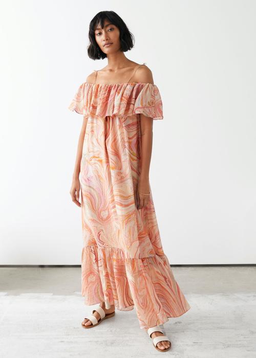 Váy trễ vai thiết kế dáng suông mang lại sự thoải mái cho người mặc. Chi tiết bèo nhún được bố trí nhẹ nhàng cho phần vai áo, chân váy.