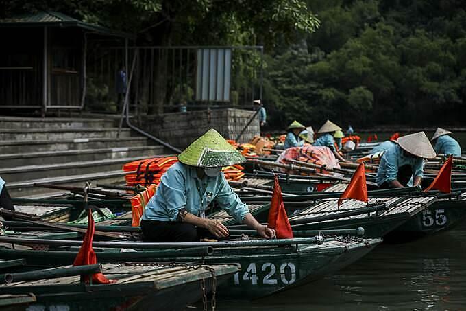 Tại điểm khởi hành, hàng dài thuyền nằm im. Những người chèo đò cũng không có nhiều việc, họ tập trung ở những gốc cây nói chuyện cho qua ngày.