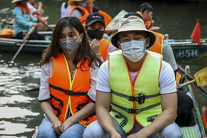 Một nhóm bạn trẻ đến từ Hưng Yên, đeo khẩu trang kín mít đi du lịch. Bọn em chọn Tràng An vì từ Hưng Yên sang khá gần, một người trong số này cho biết.