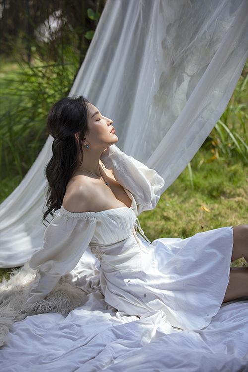 Mẫu đầm trắng trễ vai, tay bồng đi kèm chi tiết dây rút, cut-out mang tới nét gợi cảm, mong manh và phù hợp với thời trang mùa nóng.