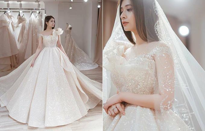 Váy cưới đính 12.000 viên đá pha lê Swarovski của nàng dâu xứ Huế Linh Chi được làm hoàn toàn bằng vải ren dệt cùng sợi đá để cô dâu thực sự tỏa sáng và lộng lẫy trong ngày trọng đại. Phần vai áo bất đối xứng là điểm nhấn đặc biệt và tôn nét điệu đà, nữ tính cho nàng dâu.