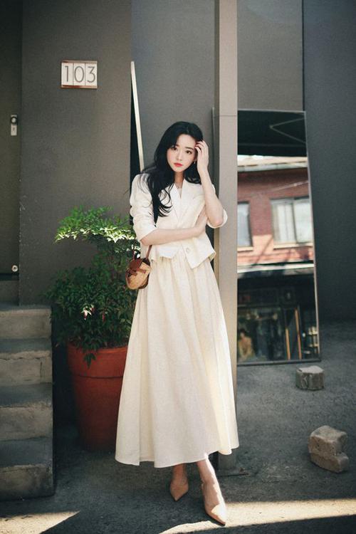 Váy liền thân màu trắng ngà kết hợp cùng áo blazer dáng lửng, túi cói và giày nude mang tới set đồ thanh lịch cho chị em công sở.