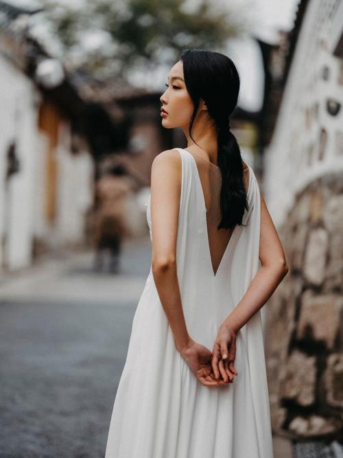 Mặt lưng váy được biến tấu với khoảng cut out chữ V, nối bởi lớp voan mỏng, giúp đem lại sự gợi cảm mà vẫn giữ được nét ý nhị cho người diện. Ảnh: Thái Phạm