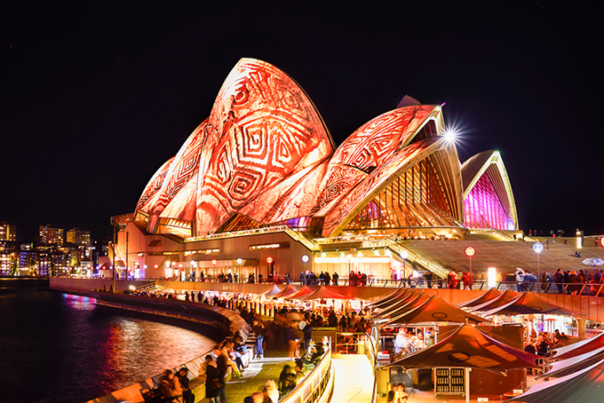 Nhà hát Con Sò - trái tim của thành phố Sydney và cả Australia - luôn là trung tâm của lễ hội bữa tiệc ánh sáng. Toàn bộ mặt ngoài của công trình sẽ trở thành sân khấu khổng lồ cho những màn trình diễn đa sắc màu. Rất đông du khách tụ tập về đây hàng đêm. Khu vực này thoáng rộng, có nhiều nhà hàng để bạn vừa hóng gió biển, vừa ngắm cảnh.