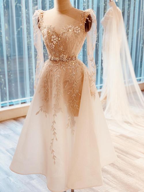 Cũng là một thiết kế tea-length (chiều dài váy đến bụng chân), điểm nổi bất của mẫu váy này đến từ phần họa tiết dây leo mềm mại trải dài theo thân váy, tạo hiệu ứng thị giác giúp dáng người cô dâu trở nên thon gọn, mình hạc xương mai.