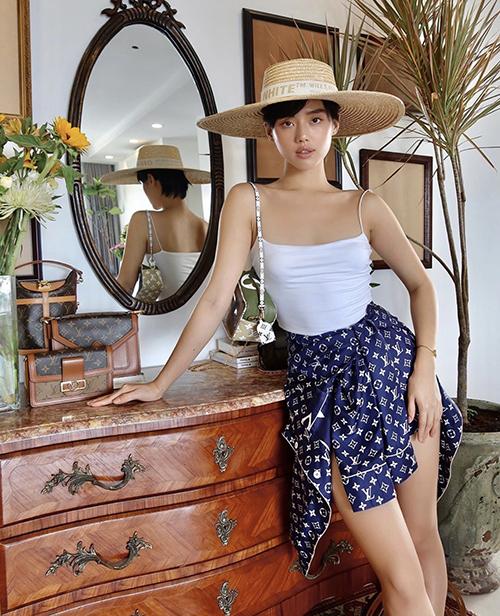Khánh Linh trẻ trung với cách phối đồ mùa hè bằng kiểu áo hai dây chất liệu vải thun. Fashionista chọn thêm mũ cói rộng vành, túi Louis Vuitton để hoàn thiện set đồ.