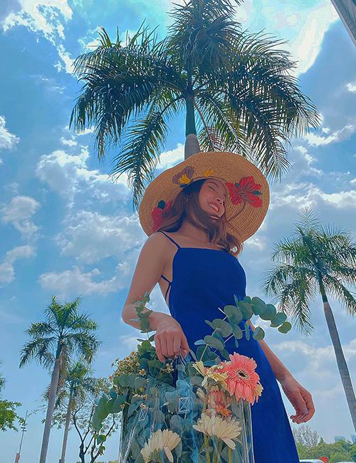 Yến Trang với hình ảnh quý cô mùa hè khi diện váy hai dây tông xanh bắt mắt cùng mũ nan, túi nhựa trong phom lớn.
