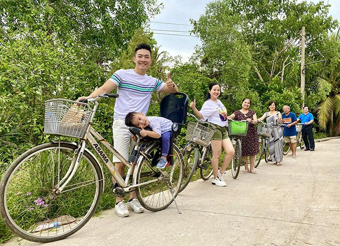 Én vàng 2006 mặc quần short trông trẻ trung, năng động đạp xe cùng chồng con và bố mẹ hai bên ngắm cảnh thiên nhiên xanh mát ở Tiền Giang.