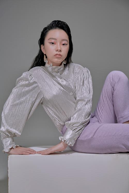 Quần tím nhạt mix áo xếp ly màu silver metallic (màu nhũ bạc) giúp cô bé nổi bật hơn. Cổ và tay áo xếp bèo nhún là chi tiết để set đồ phong cách năng động không bị cứng nhắc mà vẫn điệu đà, nữ tính.
