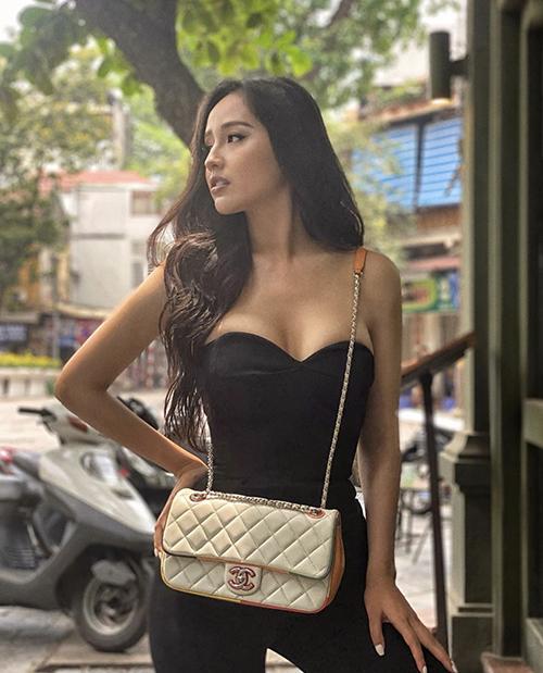 Áo cúp ngực thiết kế đẹp mắt giúp Mai Phương Thuý tôn vòng một sexy. Khi diện nguyên cây đen xuống phố, hoa hậu chọn thêm túi Chanel tông màu tương phản để phối đồ.