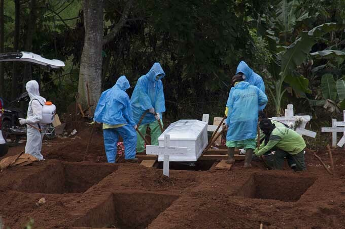 Cemetery workers burying a victim from the COVID-19 coronavirus outbreak, during a funeral in Jakarta, Indonesia, April 7, 2020
