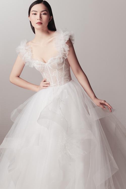 Kiểu váy hai dây dựng gọng corset mang đến vẻ ngoài trẻ trung cho nàng dâu. Bộ cánh giúp khoe khéo xương quai xanh thanh mảnh, tay thon và ngực đầy của nàng.