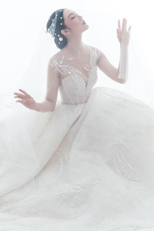 Mẫu đầm xòe nhẹ có họa tiết ren gân nổi, được điểm hạt đá lấp lánh giúp nàng dâu tỏa sáng.