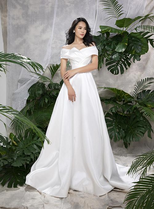 Một gợi ý khác cho cô dâu ngày hè là váy mang tên Tezza trễ vai làm từ vải satin lụa. Bộ cánh được NTK Vĩnh Thuỵ xếp ly tạo hình khéo léo, giúp mẫu đầm tối giản có sức hút. Đầm có giá bán 12,8 triệu đồng.