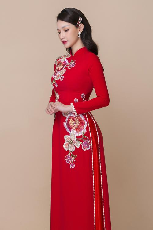 Tấm áo dài lụa đỏ được làm điệu với hàng ngọc trai đính dọc tà, viền tay áo.